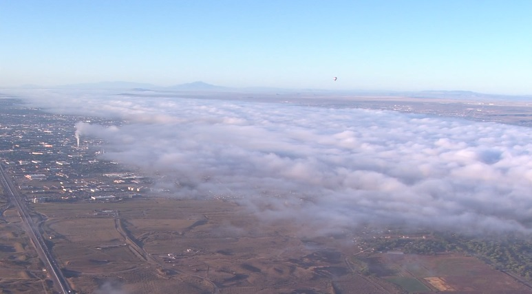A balloon floats above the morning clouds during the first morning of Balloon Fiesta.