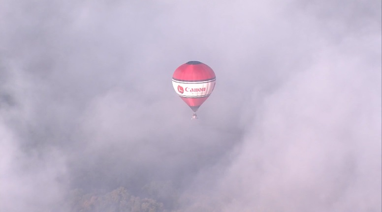 A balloon floats in the clouds above Balloon Fiesta