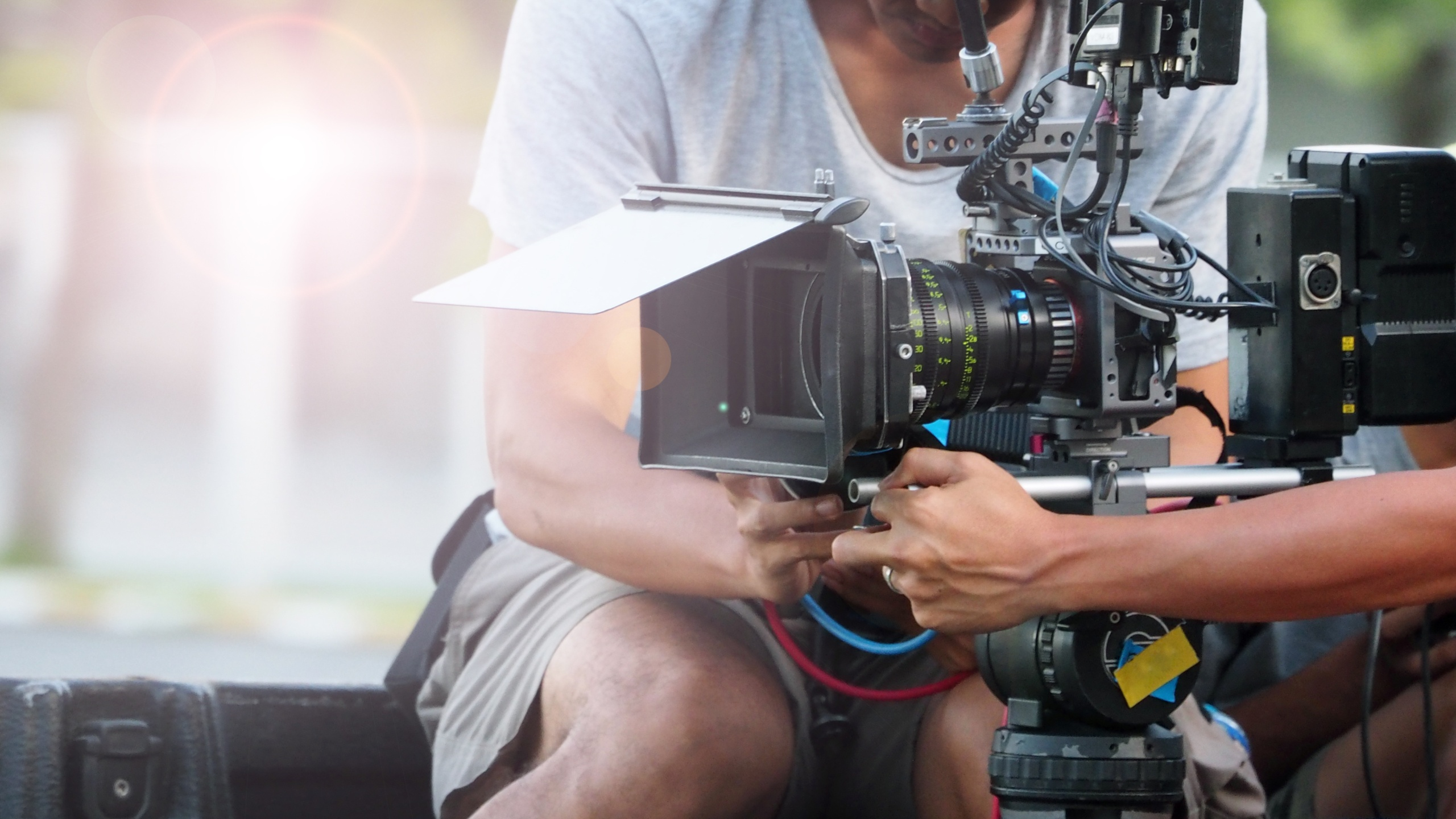 Behind the scenes of movie shooting or video production at outdoor location with high quality camera gimbal tripod equipment set up and professional film crew team on sunny day with flare lighting.